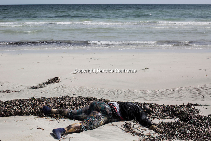 The corpse of a pregnant African migrant lays on the shore of Zawara after it was washed up by the tide. The body was among two-hundred and twenty-six bodies of illegal migrants, asylum seekers and refugees that were washed up on the shores of Zuwara and Sabratah in the week after their boats sank in the Mediterranean. Twenty-six pregnant women and one toddler were among the dead. Zawara, Libya.