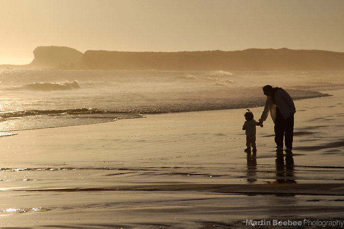 A mother and child walk along the beach at sunset in Crescent City, California