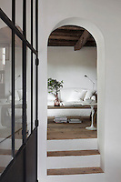 Steps through a narrow archway lead into the living area