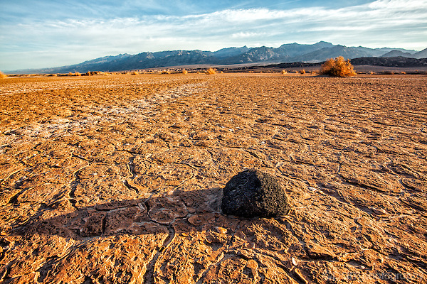 Image of lone rock on a mud flat with mountains in the distance.  Taken at Death Valley's Mesquite Dunes