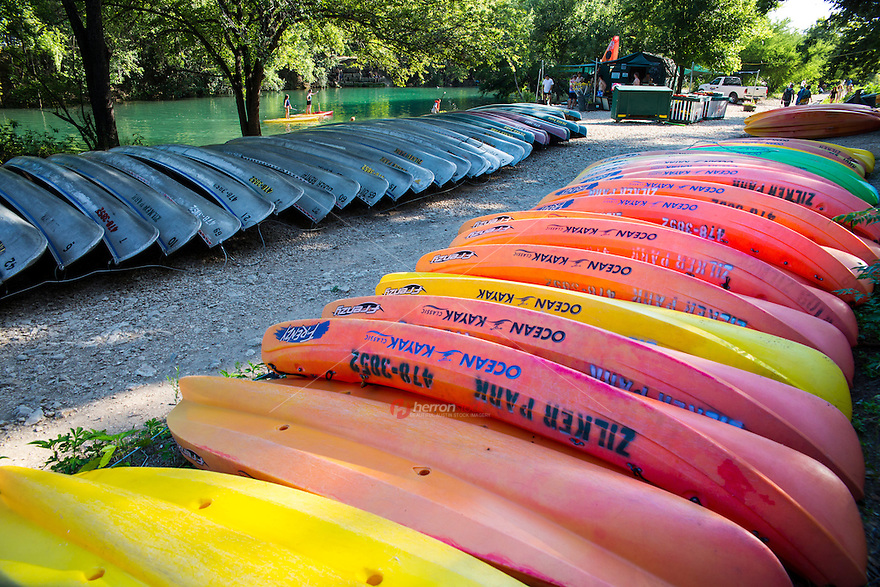 Stack of multi-colored kayaks and canoes line the banks of Barton Creek as SUP paddle boarders navigate the creek.