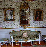 A pair of gilt-framed antique mirrors hangs above a canapé upholstered in damask in the living room