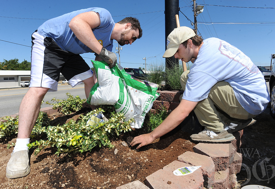 NWA Democrat-Gazette/ANDY SHUPE<br /> Brian Cain (left), co-owner of Zs Brick Oven Pizza, and Max Coppinger, a cook at the restaurant and University of Arkansas junior, work together Friday, Sept. 2, 2016, to plant a flower garden in front of the restaurant at 2730 N. College Ave. in Fayetteville. After making repairs to a water line, Cain decided to transform the spot of turned ground into a flower garden and add some curb appeal to his business.