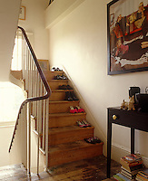 The uncarpeted staircase of this Georgian house is used to house a collection of shoes
