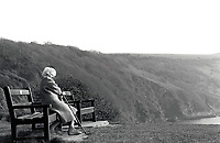 Elderly woman on bench in countryside, UK 1991
