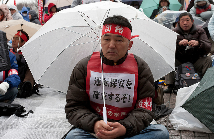 A union activist holding an umbrealla at a rally organized by Doro Chiba labour union to protest the outsourcing of what they consider essential safety and repair work and fight against rationalization of JR (Japan Railways) business. They also protested for the reinstatement of 1,047 national railway workers who lost their jobs in 1987. Shibuya, Tokyo, Japan Saturday, February 13th 2010