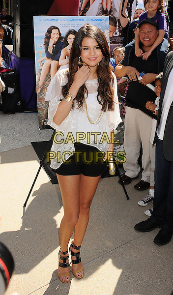 "Selena Gomez.performing at the ""Experience Monte Carlo"" With Selena Gomez Concert Series at Santa Monica Place in Santa Monica, California, USA, .June 13th, 2011.  .full length black shorts sandals beige white top smiling sheer gold earrings necklace .CAP/ROT/TM.©TM/ROT/Capital Pictures"