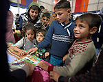 Children at a display table at a book festival in Mosul, Iraq, on November 30, 2018. The festival celebrated the rebirth of culture in the wake of the city's liberation in 2017 from control by the Islamic State group, also known as ISIS.