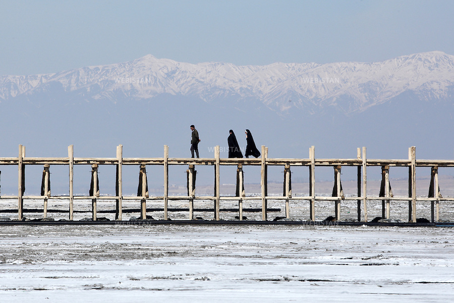 IRAN.NORTH WESTERN IRAN. ORUMIEH LAKE. 18/03/2011: A family walking on the pier in Sharafkhaneh port on dried Orumieh lake. People have to walk over 2 km to reach the water.This is the result of the fact that the Orumieh Lake in North Western Iran, the third largest saltwater lake on earth with a surface area of 5,200 square kilometers, is drying up.