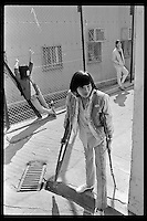 A Vietnamese refugee boy walks with crutches as he and others wait at a boat people camp in Hong Kong. Tens of thousands of Vietnamese refugees fled the Communist regime by boats to Hong Kong in 1980s.
