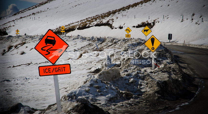 Cluster of six (6) Road signs on the treacherous Crown Range road between Queenstown and Wanaka. Winter time, snow and grit on road,  Sunny day looking down Cardona valley. Colours enhanced but the signs are for real - yep hard to believe but true!