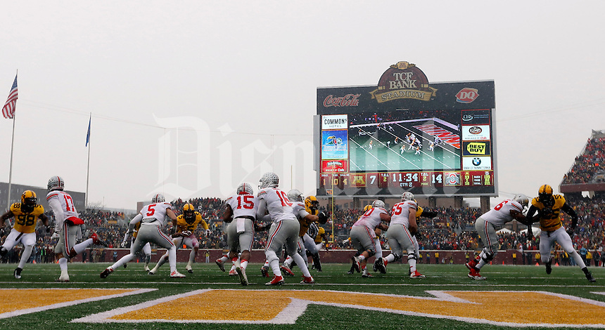 Ohio State Buckeyes quarterback J.T. Barrett (16) hands the ball off to Ohio State Buckeyes running back Ezekiel Elliott (15) against Minnesota Golden Gophers during the 2nd quarter at TCF Bank Stadium in Minneapolis, Minn. on November 15, 2014.  (Dispatch photo by Kyle Robertson)