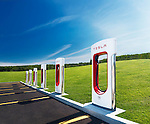 Tesla Supercharger new charging station with green nature scenery and blue sky in the background. Muskoka, Ontario, Canada. Image © MaximImages, License at https://www.maximimages.com