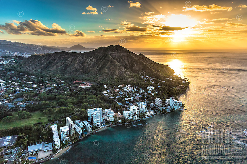 "An aerial view of the rising sun's light reflecting on the ocean along the ""gold coast"" of O'ahu, with Diamond Head at the center."