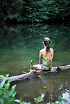 Woman sitting on a log at a quiet swimming hole