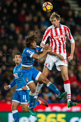 19.11.2016. Bet365 Stadium, Stoke, England. Premier League Football. Stoke City versus AFC Bournemouth. Stoke City forward Peter Crouch and Bournemouth defender Nathan Ake battle for the ball.