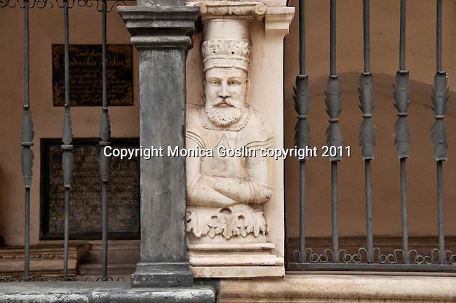 A small statue of a man on the outside of St. Mary's Church in Krakow, Poland