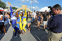1 October 2011:  Fans who have painted themselves gold and blue stop to pose for a photo on their way to the stadium prior to the game and after tailgating.  The Duke University Blue Devils defeated the FIU Golden Panthers, 31-27, at FIU Stadium in Miami, Florida.
