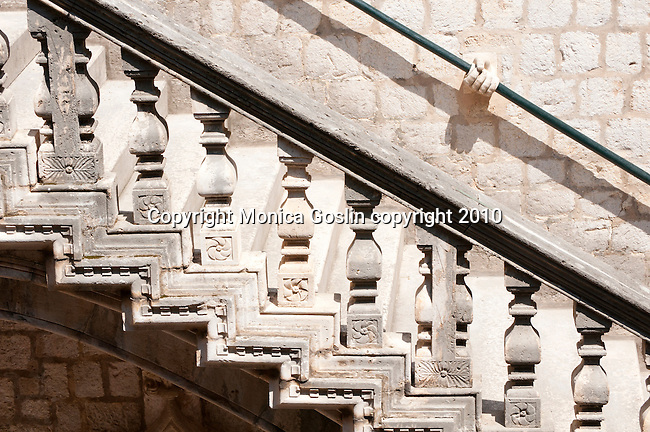 Staircase at the Rector's Palace in Dubrovnik, Croatia. The railing for the staircase is held in place by stone hands.