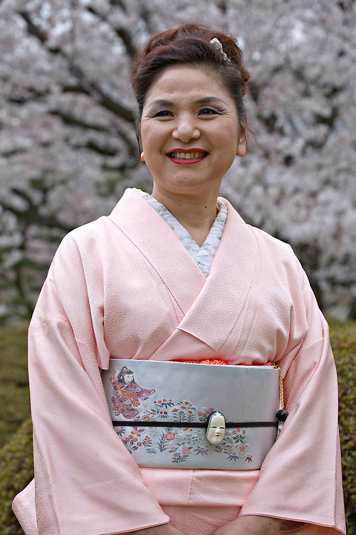 Portrait of Japanese woman wearing pink kimono among cherry blossoms