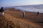 A089G8 Girl skipping on giant rope found on shingle beach with end s held my mum and brother