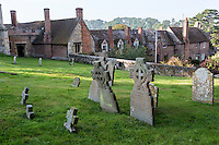 UK, England, Ewelme.  Tombstones in Cemetery of St. Mary the Virgin Church.  Parish Almshouse and School in background.