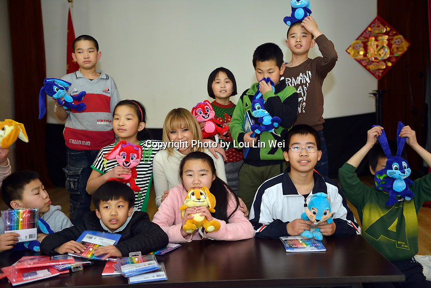 "Swiss singer and TV presenter Francine Jordi takes a group photo with students after giving presents to them while visiting ""SOS Kinderdorf"" in Tianjin, China. 22-Mar-2016"