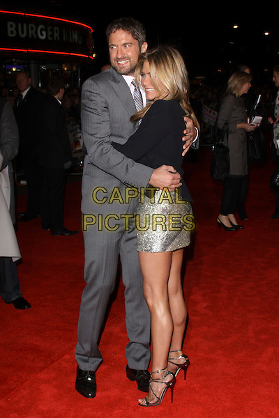 GERARD BUTLER & JENNIFER ANISTON .Attending 'The Bounty Hunter' UK film premiere at the Vue West End,cinema Leicester Square, London, England, UK. March 11th, 2010 .arrivals full length grey gray pinstripe suit arm around arms black jacket silver beaded shiny metallic dress tux tuxedo strappy open toe sandals hug embrace .CAP/AH.©Adam Houghton/Capital Pictures.