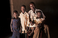 Valente Inziku with his children (L to R) Patricia Alezuyo, Joshua Tabu and Convert Diana at their home in Aribio village, Arua District, Uganda. Valente Inziko's wife Jennifer Anguko bled to death during childbirth in October 2010 in Arua Hospital. Jennifer Anguko was a local councilor and the death of her and the baby was widely reported.