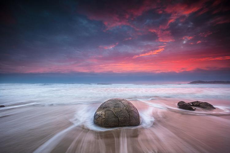 Moeraki Boulder and a fiery red dawn. Coastal Otago, South Island, New Zealand - stock photo, canvas, fine art print
