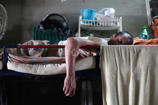 10/10/2014 -- Kirkuk, Iraq -- A Bangladeshi worker sleeps on his bed during the two hours afternoon break.