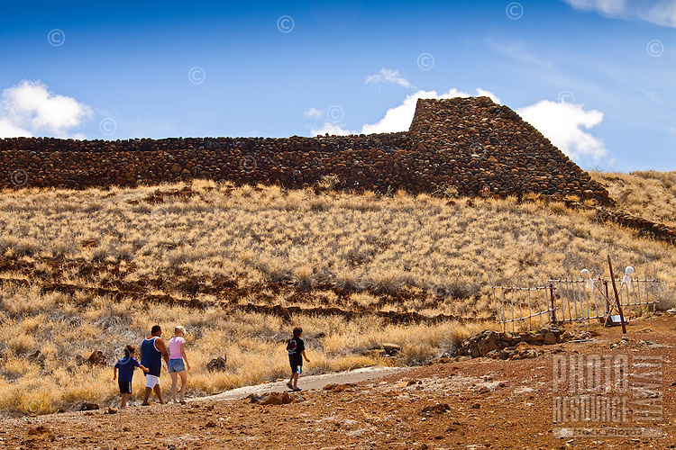 A family walking towards Pu'ukohola Heiau (a.k.a. the temple on the whale hill), the largest and last heiau constructed in 1790-91 by Kamehameha I, Pu'ukohola Heiau National Historic Site, Kawaihae, Kohala, Big Island.