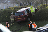 Pictured: Fire service personnel attend an incident in which a red Seat Alhambra car ended up on a grass bank at the Liberty Stadium, Wales, UK. Saturday 14 April 2018<br /> Re: An elderly driver had a lucky escape after a car ended up planted in a large hedge just metres from a busy main road.<br /> The incident, which involved a maroon Seat Alhambra people carrier one vehicle, happened at the Liberty Stadium car park on Saturday afternoon, shortly after Swansea City's 1-1 draw with Everton .<br /> The driver ended up going up the embankment alongside Neath Road, but it is not known exactly how they found themselves there.<br /> South Wales Police confirmed that the person in the vehicle was elderly.<br /> Fire personnel attended the incident.