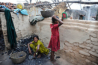 INDIA Jharkhand Dhanbad Jharia, children collect coal from coalfield to sell as coking coal on the market for the livelihood of her family, 8 years old girl Sonia and 11 year old Suman / INDIEN Jharia, Kinder sammeln Kohle am Rande eines Kohletagebaus zum Verkauf als Koks auf dem Markt , Maedchen Sonia 8 Jahre und Suman 11 Jahre, sie wohnen mit ihren Familien unmittelbar am BCCL Tagebau und sind von Umsiedlung bedroht