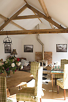 Exposed ceiling beams and a wood-burning stove create a cosy atmosphere in the living room with walls hung with photographs of agricultural buildings