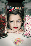 Face of a young girl, wearing red lipstick and a fancy bow, watching trough glass jars filled with candy with some lollipops in front of her.