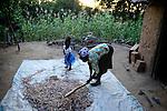 KENIA, ADS Anglican Development Services of Mount Kenya East, Stadt Embu, Dorf Gichunguri, Projekt Regenwasserauffang an einem Felsen und Speicherung in Tanks zur Nutzung in Duerreperioden, Agnes Irima, 44 Jahre, auf ihrem Hof, drischt Sorghum mit Enkelin Peace Celille, 2 1/2 Jahre