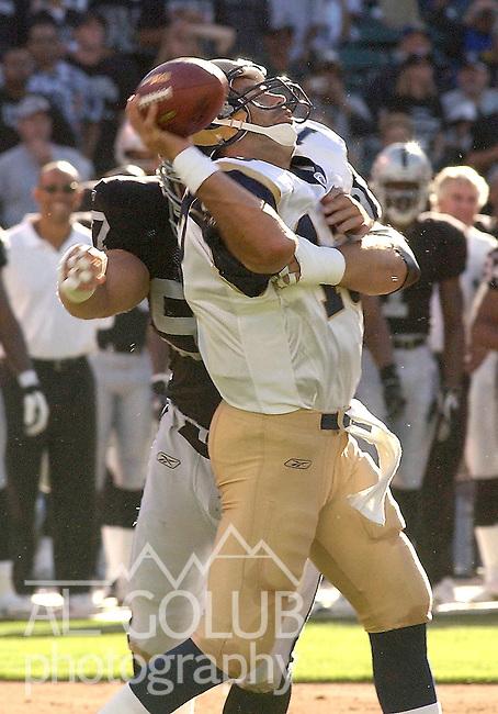 Oakland Raiders defensive tackle John Parrella (97) rushes St. Louis Rams quarterback Kurt Warner (13) on Friday, August 8, 2003, in Oakland, California. The Raiders defeated the Rams 7-6 in a preseason game.