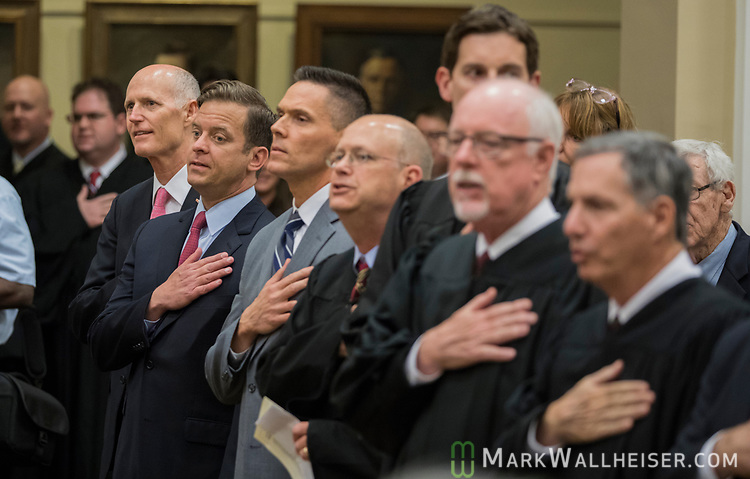 From left, Florida Governor Rick Scott, Lt. Governor Carlos Lopez-Cantera, Rep. Ross Spano, Jonathan Sjostrom, Chief Judge of the second judicial circuit, judge Fredrick Lauten, Chief Judge of the ninth judicial circuit recite the Pledge of Allegiance during the investiture of the Honorable Alan Lawson as the 86th Justice of The Supreme Court of Florida in Tallahassee, Florida