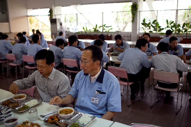 Je Hyoung Park, President of Samsung vina Electronics Co., left, eats lunch with employees at the Samsung Vina Electronics Co. factory in district Thu Duc in Ho Chi Minh City, Vietnam. Vice Lee Kyu Jin, Vice President, sits at right. Photo taken on Friday, December 4, 2009. Kevin German / Luceo Images