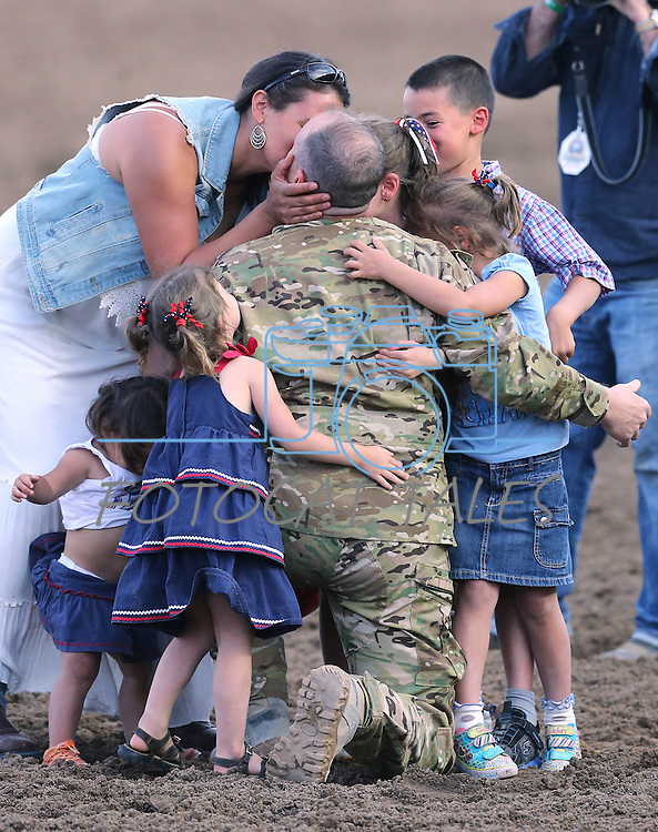 Nevada Army National Guard Chief Warrant Officer Glen Spadin gets kiss from his wife Maja after his surprise return from Afghanistan during Patriot Night at the Reno Rodeo in Reno, Nev. on Friday, June 19, 2015. Spadin returned after a year in Afghanistan to surprise his six children. <br /> Photo by Cathleen Allison
