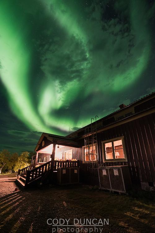 Northern lights fill sky above STF Saltoluokta Fjällstation, Kungsleden trail, Lapland, Sweden