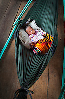 A baby in a hanging mat in one of the homes on the Tonle Sap Lake, Cambodia