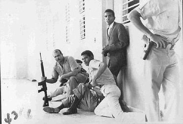 El coronel Francisco Alberto Caamaño Deñó, con fusil en mano, junto a otros militares y civiles, en un momento de pausa de los disparos en el Hotel Matum.