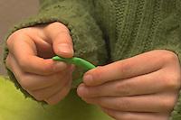 Kinder basteln Frühjahrsblumen aus Knete, Bastelei, Kind formt einen Stängel