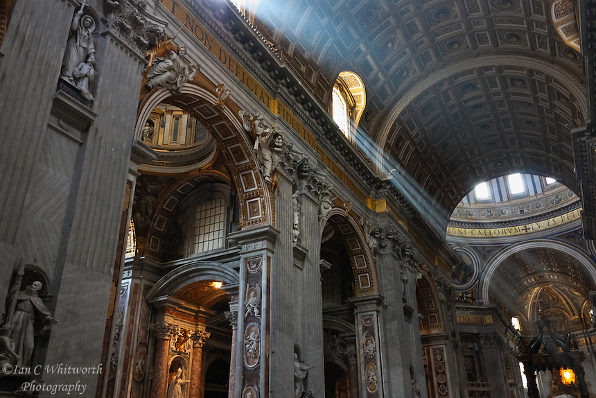 Looking up in the Vatican St Peter's Basilica at the sun streaming through the windows.