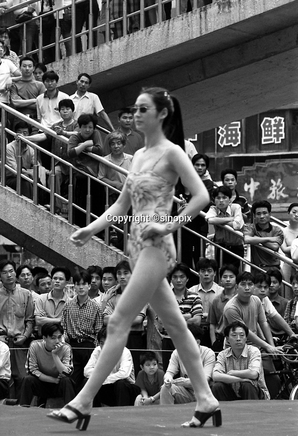Men gather around a &quot;fashion show&quot; in Shenzhen, south China. China's One Child Policy coupled with the nation-wide desire for sons has resulted in a massive gender inbalance in China.   Men are beginning to have trouble finding brides in areas and the black-market trade in women and girls is getting worse.<br /> Apr 2000<br /> <br /> photo by Richard Jones / Sinopix