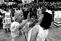"""An unidentified Mae, performs a """"santiguado"""", the cleaning of the aura of a person from negative energies, during celebrations of Yemanja, , the """"Goddess of the Sea"""", in Ramirez beach, Montevideo, Uruguay. Acoording to Mae Susana about 500.000 people take part in the celebrations, part of them believers of the Umbanda religion, and part of them believers of other religions. Believers pay tribute February 2 to Yemanja, asking for work, love and money. Photo by Quique Kierszenbaum"""