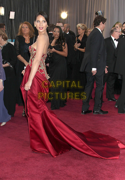 Olivia Munn (wearing Marchesa).85th Annual Academy Awards held at the Dolby Theatre at Hollywood & Highland Center, Hollywood, California, USA..February 24th, 2013.oscars full length red gold embroidered strapless silk satin dress train side looking over shoulder .CAP/ADM/RE.©Russ Elliot/AdMedia/Capital Pictures.