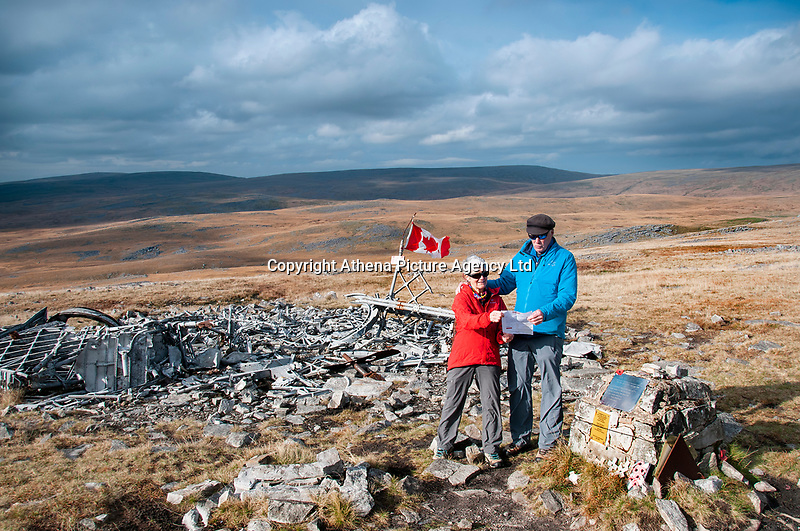 """Pictured: Dr Peter Pare (R) with his wife by the wreckage of the Wellington Bomber MF509 in the Brecon Beacons, Wales, UK. <br /> Re: The nephew of a World War II airman whose plane crashed into a Welsh mountain has climbed the peak to pay tribute to the uncle he never met.<br /> Dr Peter Paré, 74, travelled from his home in Vancouver, Canada, to read a poem at the desolate spot where his uncle Bill Allison was killed.<br /> Flying officer Allison, 28, was one of the six crew of a Wellington Bomber that crashed on a training flight in November 1944.<br /> The plane wreckage is still scattered over Carreg Goch in the Brecon Beacons where hundreds of young airmen learned to prepare for bombing missions.<br /> Dr Paré said: """"I wanted to make this pilgrimage even though I was a baby when he died and never met Bill Allison.<br /> """"We only found out about the crash site recently and it is remarkable that so much of the plane is still here.""""<br /> Flying officer Allison was the oldest on board when the plane's starboard engine developed a fault during a low-flying exercise.<br /> For years local people have honoured the brave airmen by flying a Canadian flag at the scene - replacing it every time it gets ripped by strong winds.<br /> Dr Paré, retired Professor of Medicine at the University of British Columbia, said: """"It was very moving to see the Maple Leaf flying where my uncle died all those years ago.<br /> """"It brought a tear to my eye as I read the poem I wrote in his honour."""""""